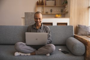 Stock image of man on sofa with laptop